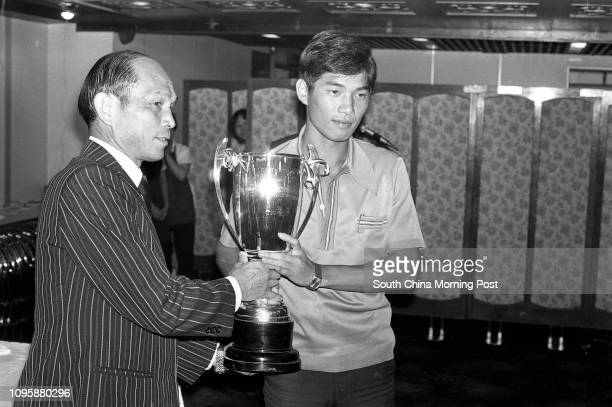 Suen Chehang representative of the Police soccer team receives the Senior Youth Cup from Henry Fok Yingtung President of the Hong Kong Football...