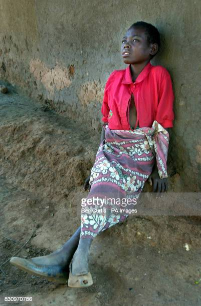 AIDS sufferer Ku Nthata whose parents also died of AIDS outside her hut in Mphanda village in central Malawi * The United Nations currently estimates...
