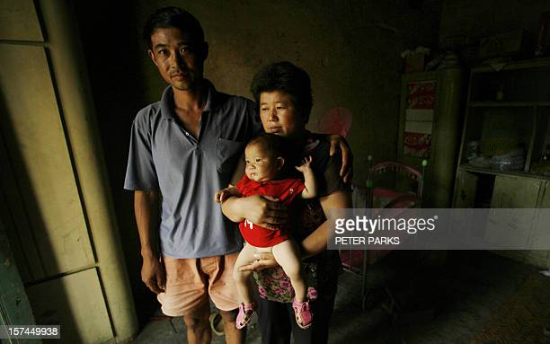 AIDS sufferers Cao Xiaonian and his wife Zhou Xiaoneng hold their 9monthold baby in their village home in China's southern Henan province 02 August...