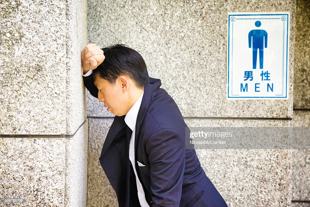 Suffering Japanese businessman rests against WC wall feeling sick : Stock Photo