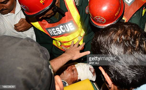 Suffering with head injuries Pakistani politician and former cricketer Imran Khan is carried by rescuers as they rush to the hospital in Lahore on...