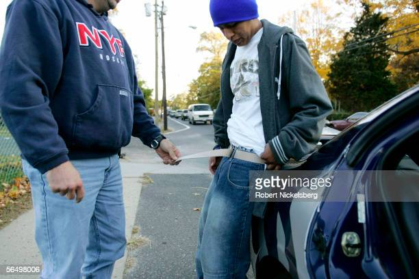 Suffolk County Police officers from the antigang unit check Francisco Javier Garcia a Salvadoran native and suspected gang member of Mara Salvatrucha...