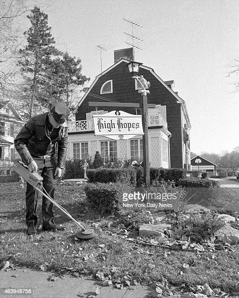 Suffolk County policeman uses mine detector as he sweeps through dead leaves on lawn of Ronald DeFeo's 12room $75000 Dutch colonial home in...