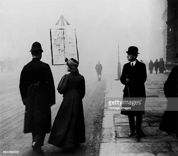 A suffragette demonstrating in Whitehall London c1908 Her placard says 'Give Women the Vote this Session' The arrow at the top of the placard...
