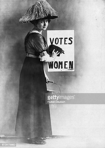 A suffragette pasting up a bill poster calling for Votes for Women