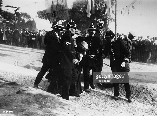 A suffragette who was attacked in the crowd at a meeting given by the Chancellor of the Exchequer David LloydGeorge at Criccieth being escorted from...