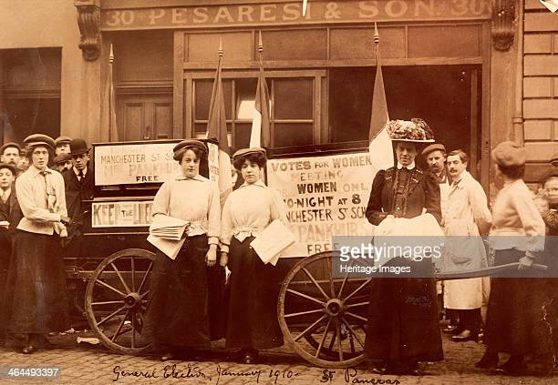 Suffragettes advertising a talk by Emmeline Pankhurst during the General Election St Pancras London 1910 The women use handcarts for their posters...