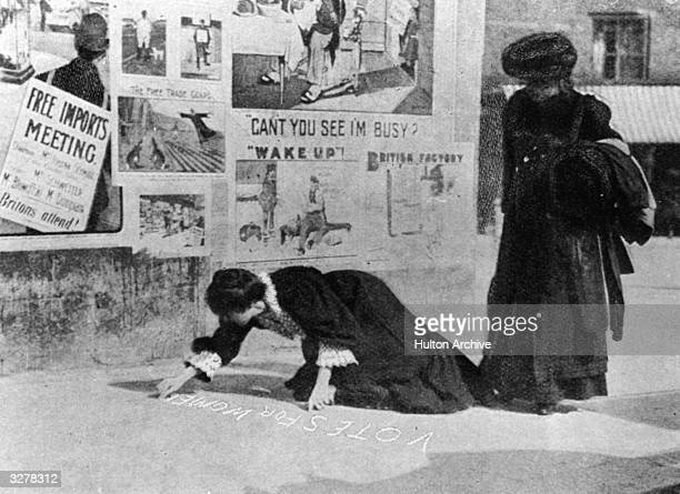 Suffragettes Annie Kenney and Mary Gawthorne painting a pavement with a slogan 'Votes For Women' during the Hexham byelection