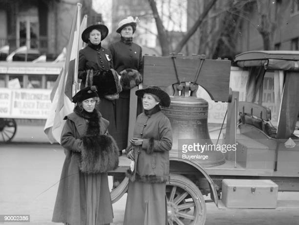 Suffragettes in Fur Adorned Coats and Mink Muffs stand in front of a Liberty Bell Replica which will accompany them in parade