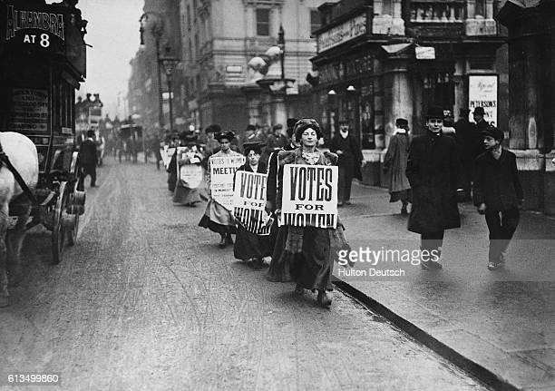 Suffragettes walk along a London street wearing sandwich boards demanding that women be given the vote 1912