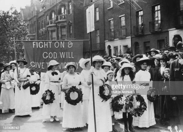 Suffragettes wearing black armbands in the funeral procession of English suffragette Emily Davison London 14th June 1913 Davison died after she ran...