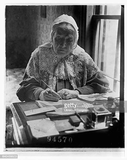Suffragist and author of the famous American poem Battle Hymn of the Republic Julia Ward Howe writes at a desk near a window