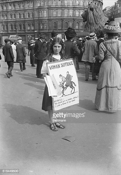 Suffragists in England Young girl as placard bearer during suffragist demonstration Placard depicts political cartoon with the caption Mrs Bull We...