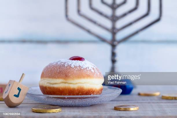 sufgania, dreidels, menorah ,hanukkah coins or hanukkah gelt. wood background. translation: n - sufganiyah stock pictures, royalty-free photos & images