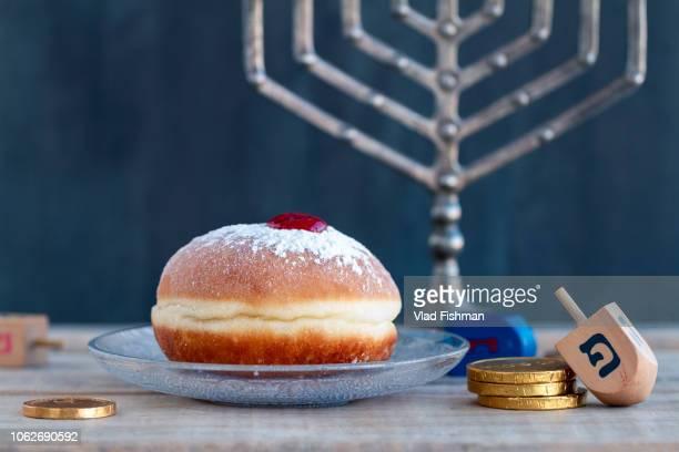 sufgania, dreidels, menorah ,hanukkah coins or hanukkah gelt. wood background. translation: p - sufganiyah stock pictures, royalty-free photos & images