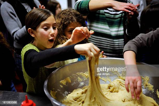 Sufganiyot19a Jess Carrel 10 and Myah Friedman 9 pull out their dough frrom a mixing bowl prepared by Pastry Chef Sandra Adams as she teaches 4th...