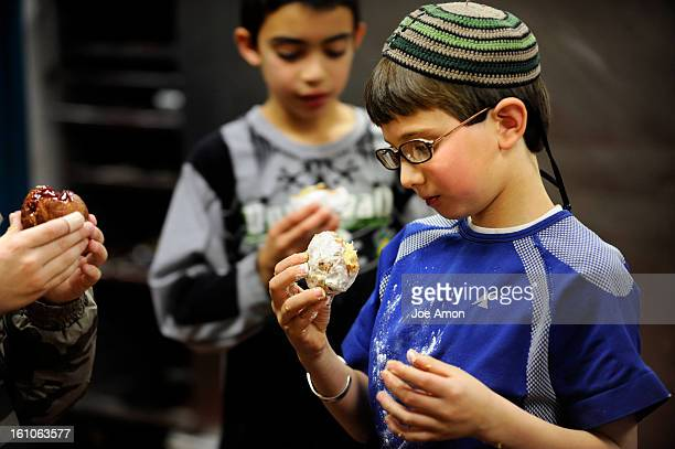 Sufganiyot19c Abe Rosenthal 9, tries out his handy work after Pastry Chef Sandra Adams taught the 4th grade students from Herzl/RMHA how to make...