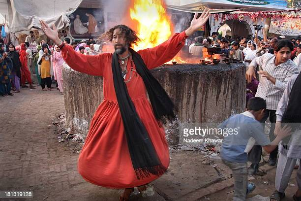 Sufi Malang swirling in front of fire which is actually the burning candles in mass. According the traditions people burn the candles and lamps of...