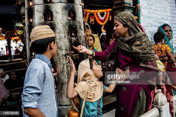 Sufi Muslim woman moves to apply dark black eyeliner collected from candles to the eyes a girl at the 'dargah' or shrine of Sufi saint Muhammad...
