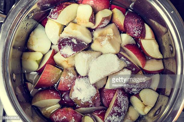 Sugar and pieces of apples in a cooking pot for preparing applesauce