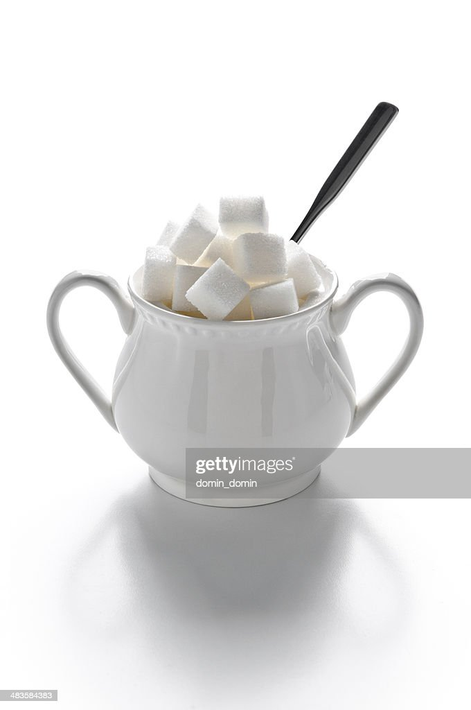 Sugar bowl full of sugar cubes and spoon, isolated on white : Stock Photo