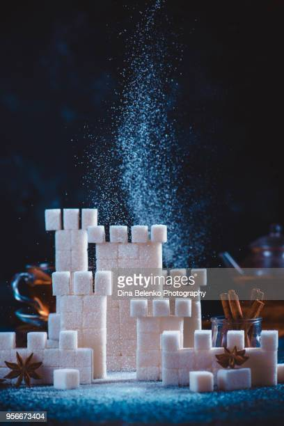 sugar castle siege with falling sugar, teapot, cinnamon and spices. tower built out of sugar cubes. conceptual still life photography with copy space. - glycemia stock pictures, royalty-free photos & images