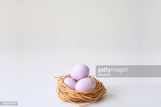 sugar coated chocolate eggs in a string nest - animal nest stock pictures, royalty-free photos & images