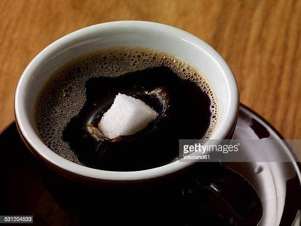 sugar cube in cup of coffee - sugar coffee stock photos and pictures