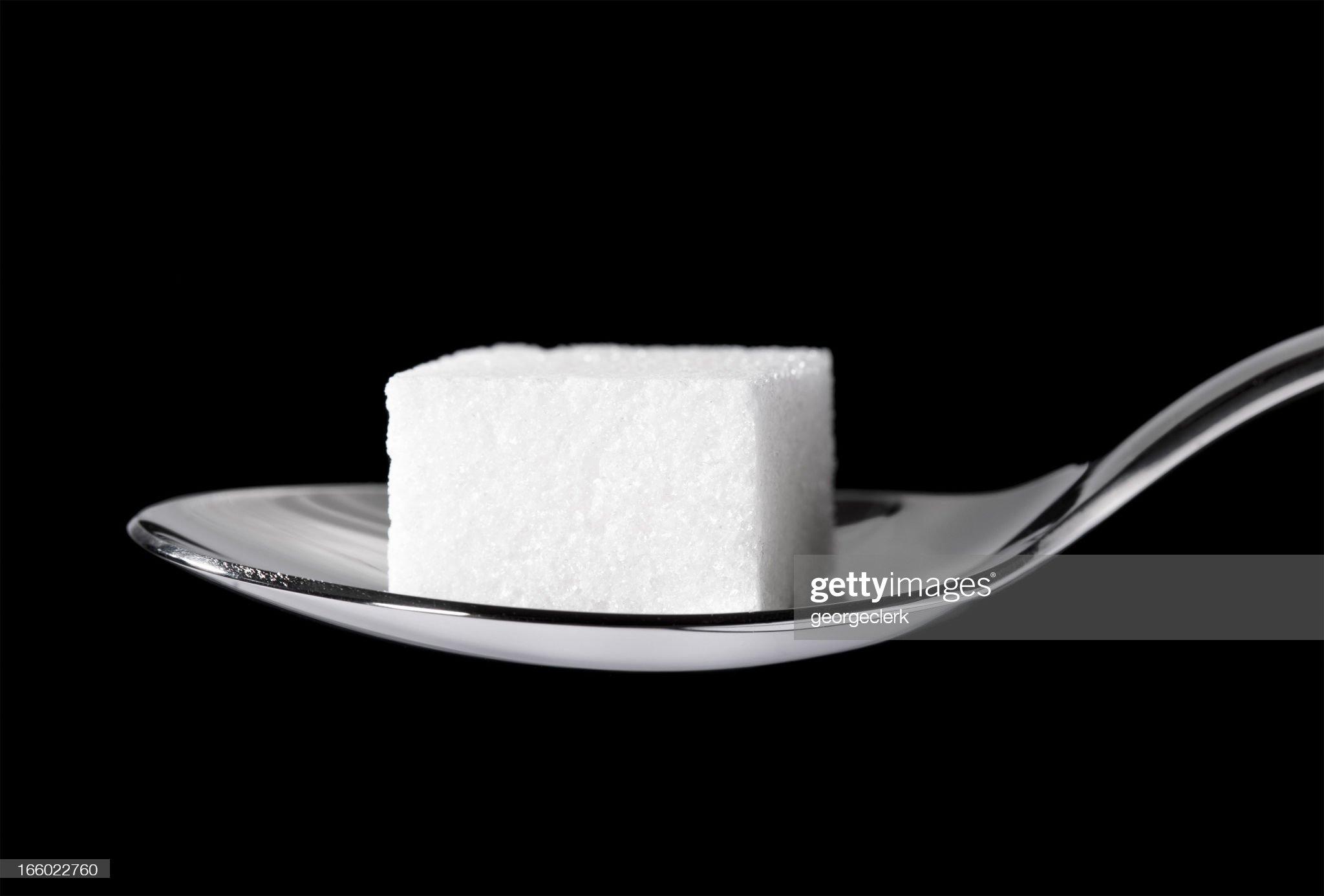 Cubo de azúcar en una cucharadita : Foto de stock
