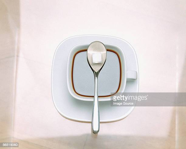 sugar cube on spoon - sugar coffee stock photos and pictures