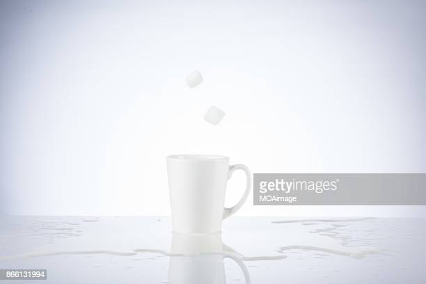 Sugar cube splashing in the cup of milk