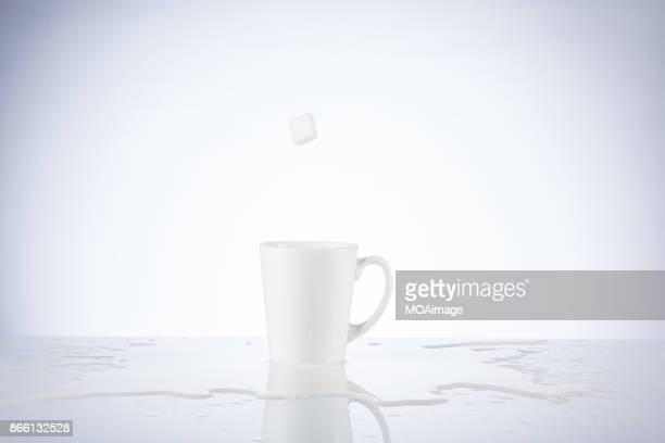 Sugar cube splashing in the cup of milk