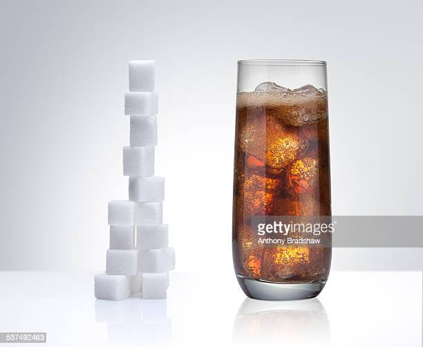 Sugar cubes besides a glass of cola