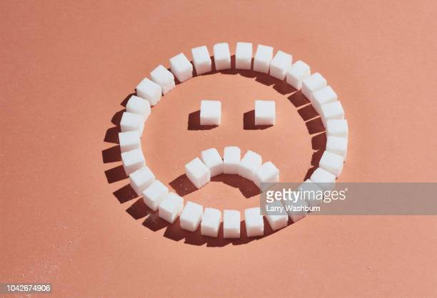 Sugar cubes forming frowning face on peach background