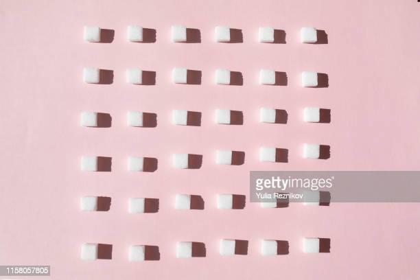 sugar cubes on pink background - fülle stock-fotos und bilder
