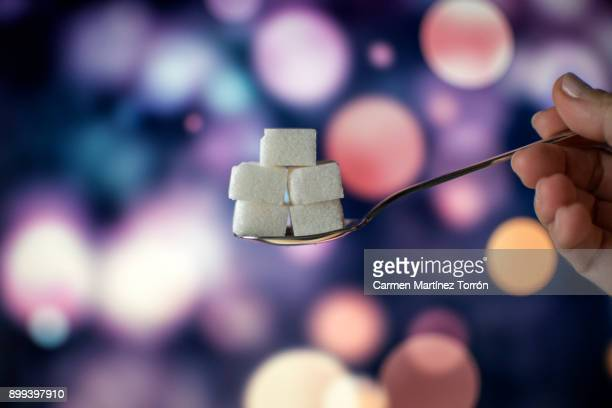 Sugar cubes on teaspoon.