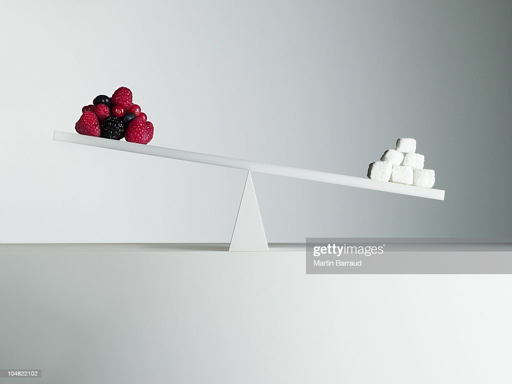 Sugar cubes tipping seesaw with berries on opposite end : Stock Photo