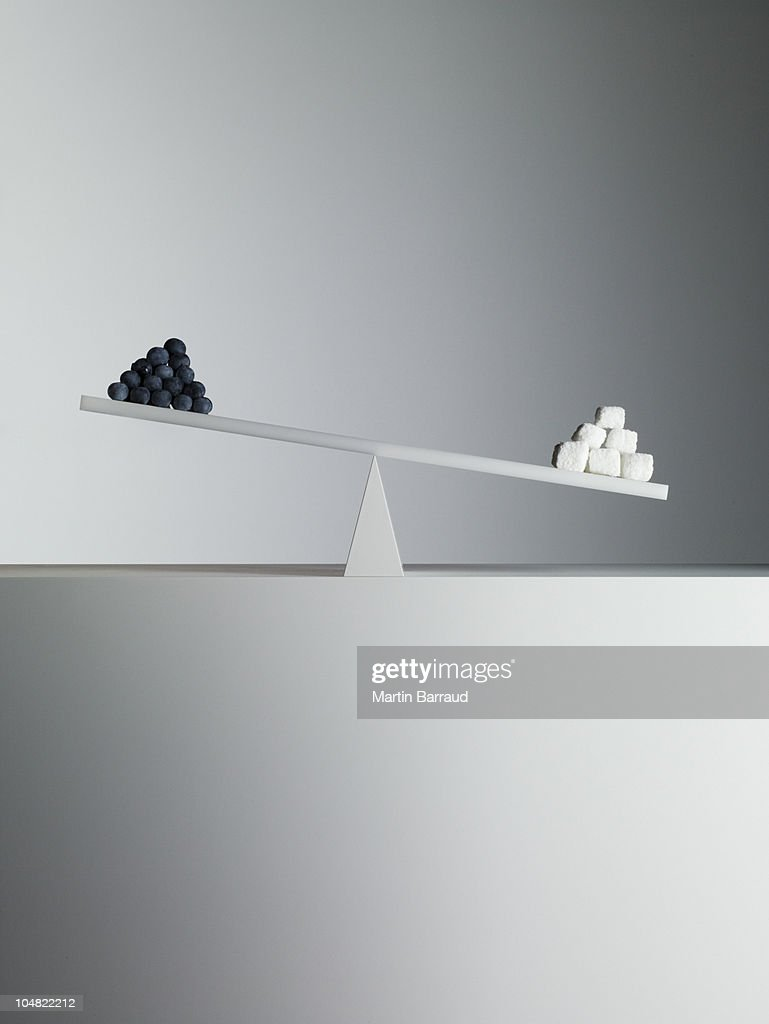 Sugar cubes tipping seesaw with blueberries on opposite end : Stock Photo