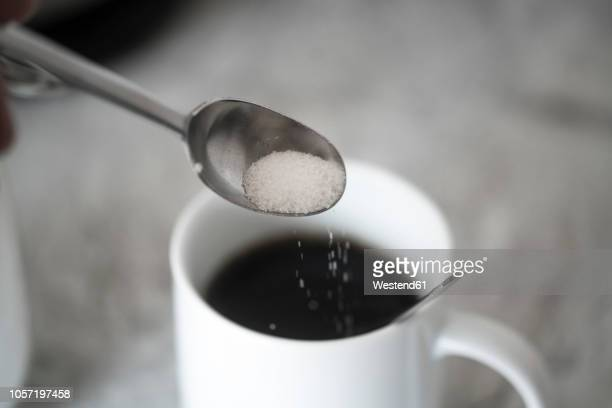 sugar on coffee spoon in front of mug with black coffee - sugar coffee stock photos and pictures