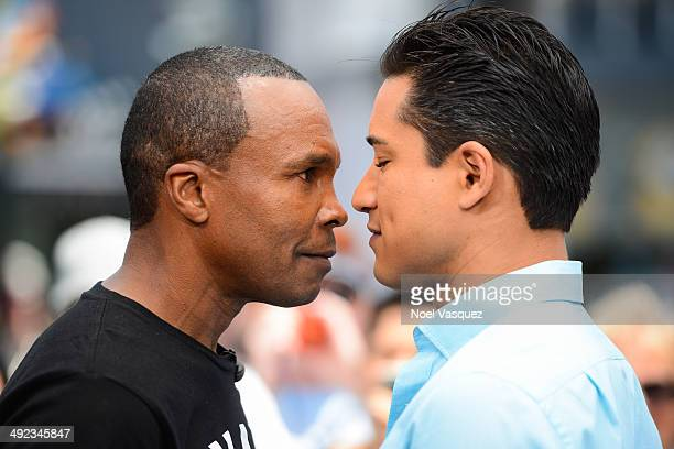 Sugar Ray Leonard and Mario Lopez stare down each other at 'Extra' at Universal Studios Hollywood on May 19 2014 in Universal City California