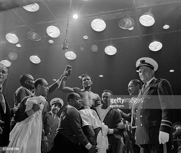 Sugar Ray Robinson smiles broadly as he is raised to shoulders of his handlers here, after scoring a 2nd round knockout over defending champ Carl...