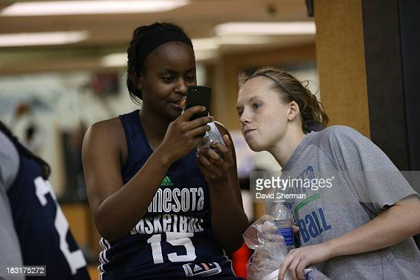 Sugar Rogers and Lindsey Moore of the Minnesota Lynx look at a phone photo during practice before the 2013 WNBA Finals on October 5 2013 at Target...