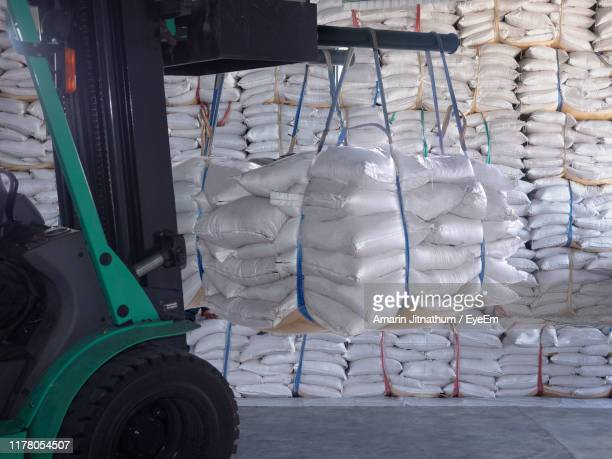 sugar sacks hanging on forklift in factory - sack stock pictures, royalty-free photos & images