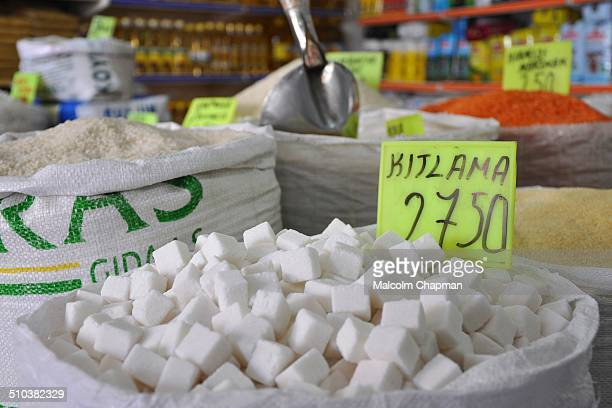 Sugar sold loose by weight from sacks in a grocery store in Bergama Turkey Kitlama style tea is where the drinker holds the oblong sugar cube between...