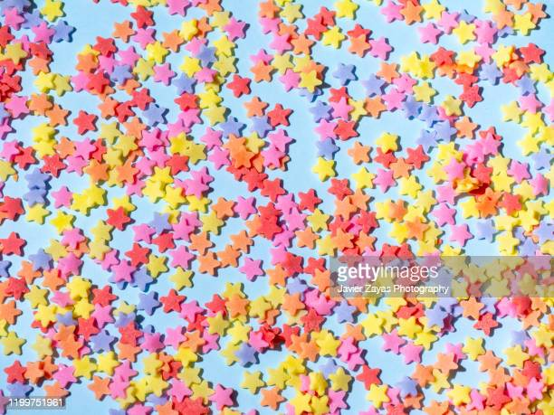 sugar stars on blue background - star shape stock pictures, royalty-free photos & images