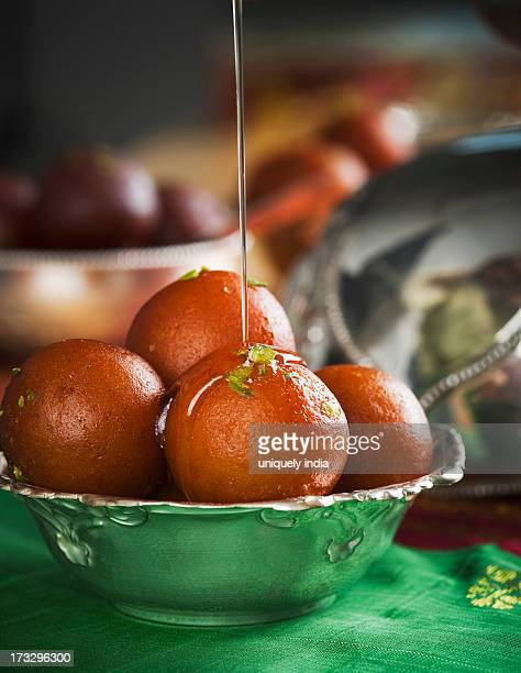 Sugar syrup being poured on gulab jamuns in a bowl