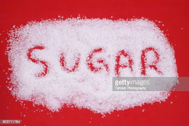 sugar written in white sugar - sugar pile stock pictures, royalty-free photos & images