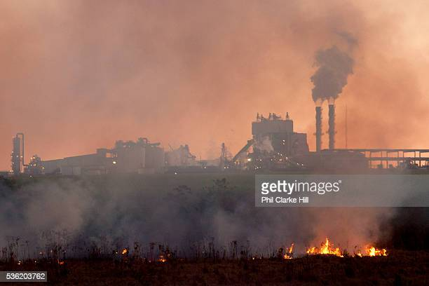 Sugarcane ethanol processing plant with burning Cerrado in the foreground. Exterior view. Brazil is the largest producer of Sugar and Beef, then...