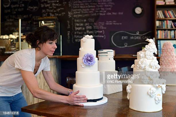 A 'Sugarplum cake' employee decorates a wedding cake for US residents in France on October 26 2012 in Paris From 'Kate'inspired lace dresses to...