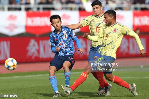 Sugawara Yukinari of Japan and Jaime Alvarado of Colombia compete for the ball during the U-22 international friendly match between Japan and...